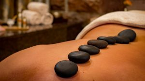Lady receving a hot stones massage treatment