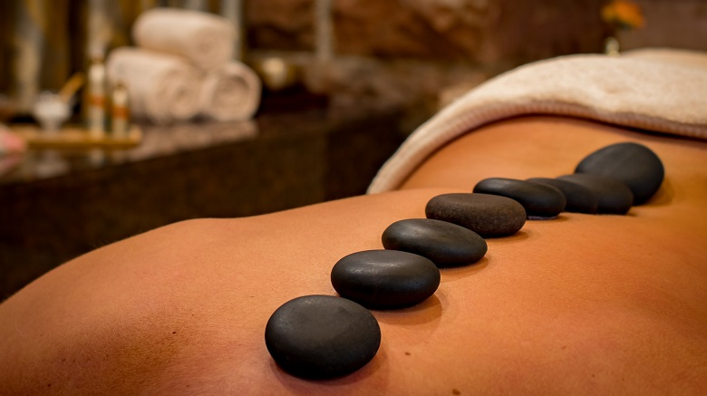 Lady receving a hot stones massage treatment